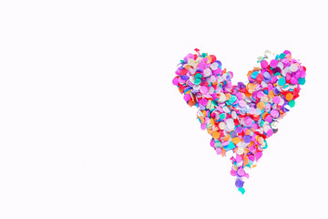 Heart of colorful confetti on white background, concept of Valentine's day. Close up. Top view.