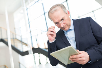 Manager schaut erstaunt auf seinen Tablet Computer