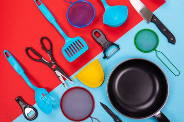 Close up portrait of frying pan with set of kitchen utensils on red-blue background