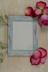 Empty photo frame with rose flower and petals