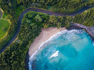 Aerial view of the sandy beach and curved asphalt road on the west coast of Maui. Hawaii