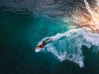 Wall Mural - Bodyboard surfer rides tropical wave at sunset
