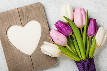 Fresh colorful tulips and heart shaped frame