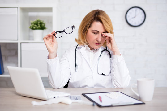 stressed or tired mature female doctor working in modern office
