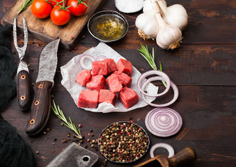 Raw lean diced casserole beef pork steak with vintage meat hatchet and knife and fork on wooden background. Salt and pepper with fresh rosemary, red onion and garlic.Space for text