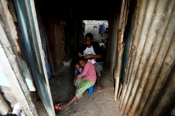 A woman combs her daughter's hair while she breast-feeds her son as she sits at the entrance of the house in Ouakam neighbourhood, Dakar,