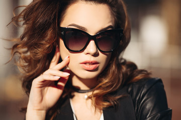 Gorgeous brunette woman with plump lips, sensuality touching face skin and posing at camera in windy weather. Beautiful girl in sunglasses, with curly hair and perfect manicure after beauty salon.