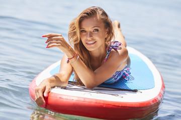 beautiful young girl in sportswear sitting on a SUP board