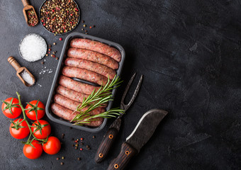 Raw beef and pork sausage in plastic tray with vintage knife and fork on black background.Salt and pepper with tomatoes and rosemary.Space for text