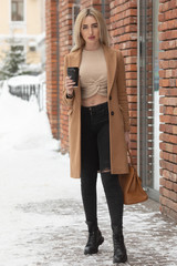 lifestyle and people concept: Smiling stylish young woman drinking coffee while walking on a city street