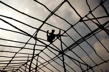 A worker works on roof for a shelter for tsunami victims in Panavalan Kudi, south India.