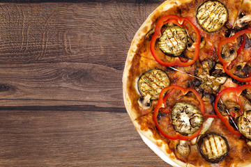 Tasty delicious fresh pizza on plate on wooden background. Photo for menu, italian food concept