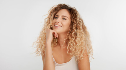 head and shoulders plan of blonde wooman with big curly hair in studio on white smiling