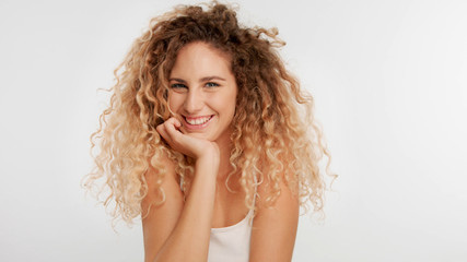 head and shoulders plan of blonde wooman with big curly hair in studio on white laughing with head on arm