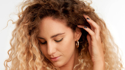 closeup portraitof green eyed model with big curly blonde hair, ideal skin watching down and put her hair behind the ear