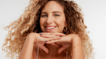 closeup portrait of blonde model with curly hair put her chin on two crossed hands happy smiling, blowing hair
