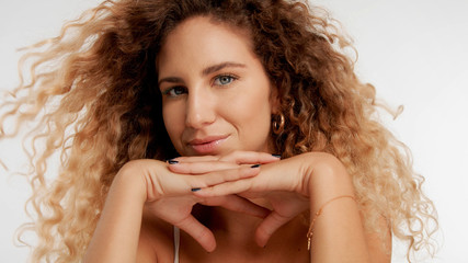 closeup portrait of blonde model with curly hair put her chin on two crossed hands tilt her head and watching to the camera, her hair is blowing