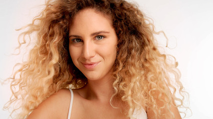 closeup portrait of model with big curly blonde hair blowing and she is smiling has flirty glance