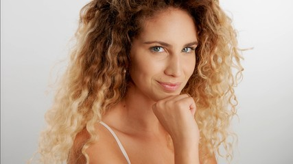 serios flirty glance of blonde model with curly hair