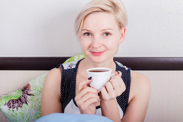 Young beautiful blonde woman with short hair sitting on her bed and holding a hot drink