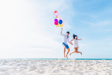 Happiness lover couple holding colorful balloons and jumping with smile on the tropical beach in...