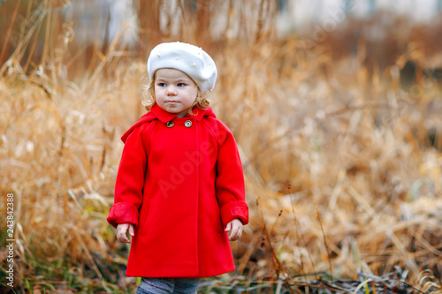 c745836e5fe Outdoor portrait of little cute toddler girl in red coat and white fashion  hat barret. Healthy happy baby child walking in the park on cold day.