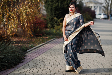 Elegant brunette south asian indian girl in saree walking outdoor.