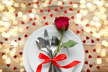 valentines day and romantic dinner concept - close up of red rose flower on set of dishes with cutlery and hearts on wooden table
