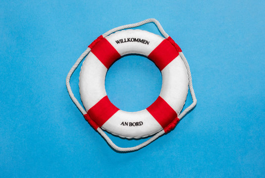 """Lifebelt with lettering """"Willkommen an Bord"""" in german language (translates to """"Welcome on board"""") on blue paper background"""