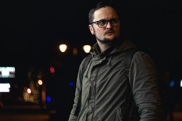 Portrait handsome young man with a beard and mustache. glasses. cold season, military style clothing. on the street in the city at night