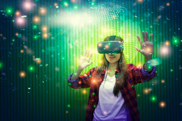 Portrait of young woman using virtual reality or VR for gaming and video that showing stars in the galaxy space. Future technology for entertainment at home.