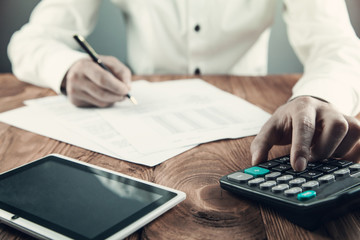 Businessman using calculator in his desk.