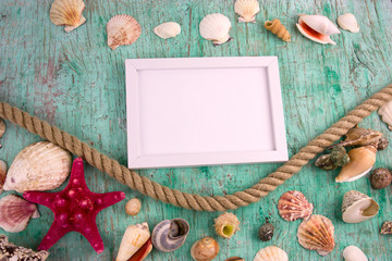 white wooden blank frame,rope and the collection of sea shells on a vintage shabby background