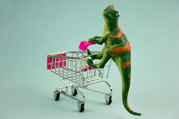 plastic green dinosaur with shopping cart on blue background