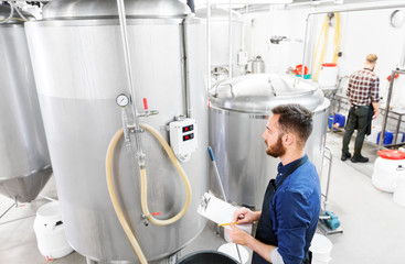 manufacture, business and people concept - man with clipboard working at craft brewery or beer plant