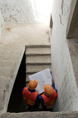 Civil engineers analyzing construction plan when walking up the stairs, view from above
