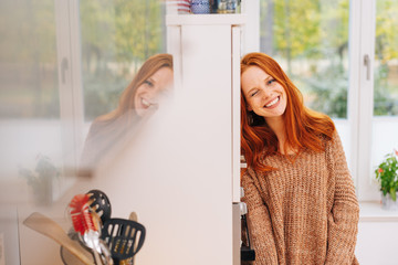 Woman winking at camera, standing in kitchen