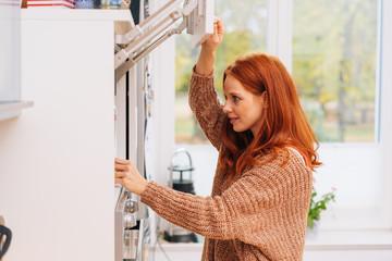 Woman peeks into kitchen cupboard