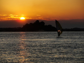 Person training windsurf in the holidays with the sunset in the background