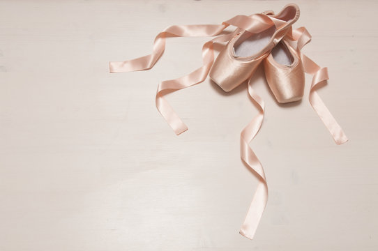 Pair of two satin ballet shoes with long ribbons lying on a white wooden background