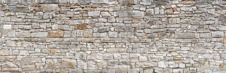 Fototapeten Steine Panorama - Alte graue Mauer aus groben, vielen kleinen, rechteckig gehauenen Natursteinen