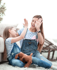 mother and her little daughter give each other a high five