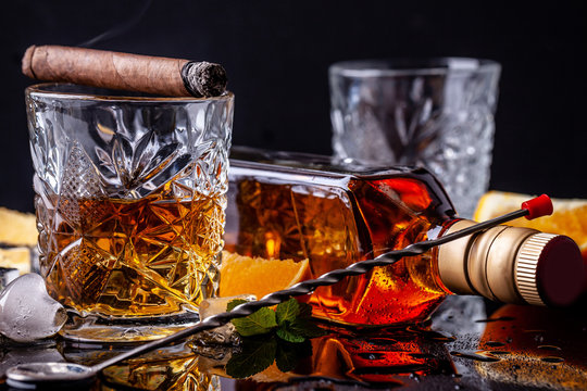 concept of alcoholism, loneliness, dependence. A bottle of whiskey, a glass of whiskey and with ice, a cigar with smoke on a black table, on a black background. Elite drink for masculine relaxation
