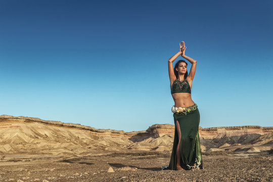 Woman dancing to the famous belly dance with natural sunset light, in the Namibe Desert with canyons. Africa. Angola.