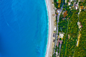 Aerial view from top to bottom of the turquoise sea with green trees
