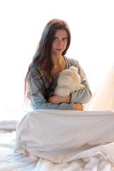 langhaarige Frau umarmt Teddybär
