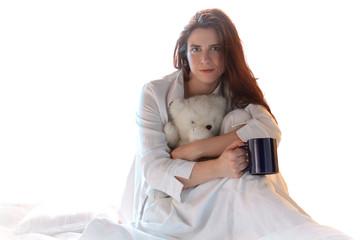 Frau mit Teddybär und Tasse im Bett