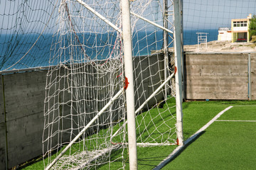 Part of soccer goal door with white net. Close up for football goal at soccer field with green...