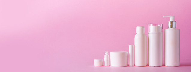 White cosmetic tubes on pink background with copy space. Skin care, body treatment, beauty concept. Banner