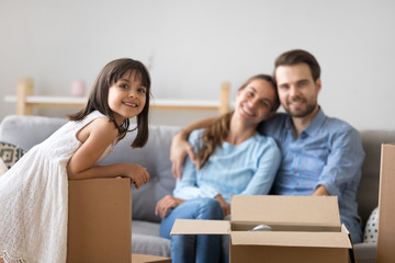 Portrait of happy kid girl posing with cardboard boxes on moving day with smiling parents at background, cute little child daughter looking at camera in new home enjoying family relocation concept